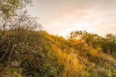 Πανόραμα τοπίων ηλιοβασιλέματος, λόφοι στη χρυσή ώρα, μικρό χωριό στην κοιλάδα, όμορφα χρώματα και σύννεφα Στοκ Εικόνες