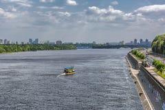 Πανόραμα του Κίεβου, ποταμός Dnipro, Ουκρανία Η άποψη από τη για τους πεζούς γέφυρα Το κίτρινο σκάφος μηχανών επιπλέει προς τα κά Στοκ Φωτογραφίες