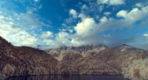 Πανόραμα των βουνών και του όμορφου ουρανού κοντά στη λίμνη στοκ φωτογραφίες