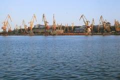 Πανόραμα των γερανών λιμένων πέρα από το μπλε ουρανό και τη θάλασσα Στοκ φωτογραφία με δικαίωμα ελεύθερης χρήσης