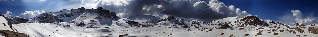 Πανόραμα των χιονωδών χειμερινών βουνών με το μπλε ουρανό και τα σκοτεινά σύννεφα Στοκ Φωτογραφία
