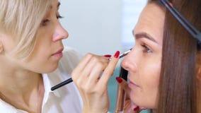 Παν πυροβολισμός της νέας γυναίκας που παίρνει hairstyle και makeup από τους επαγγελματίες φιλμ μικρού μήκους