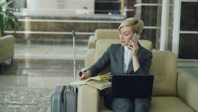 Παν πυροβολισμός της ξανθής πολυάσχολης συνεδρίασης επιχειρηματιών στην πολυθρόνα στο λόμπι ξενοδοχείων που μιλά το κινητό τηλέφω φιλμ μικρού μήκους