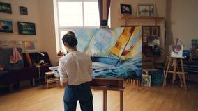 Παν πυροβολισμός της σοβαρής εργασίας ζωγράφων κοριτσιών επαγγελματικής στο στούντιο που χρωματίζει το θαλάσσιο τοπίο με το κράτη φιλμ μικρού μήκους
