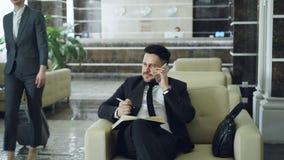 Παν πυροβολισμός της όμορφης γενειοφόρου συνεδρίασης επιχειρηματιών στην πολυθρόνα που μιλά το κινητό τηλέφωνο με το σημειωματάρι απόθεμα βίντεο