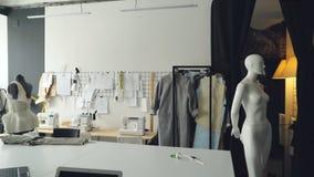 Παν πυροβολισμός του ελαφριού στούντιο σχεδίου ιματισμού με το μεγάλο γραφείο ραφτών ` s, μανεκέν, πολυάριθμα σκίτσα που καρφώνον απόθεμα βίντεο