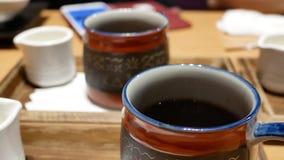 Παν πυροβολισμός του καυτού μαύρου τσαγιού στον πίνακα μέσα στο ιαπωνικό εστιατόριο απόθεμα βίντεο