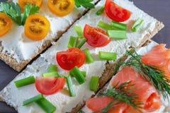 Παξιμάδι με το μαλακό τυρί, την πέστροφα, τις ντομάτες, τον άνηθο και τα πράσινα κρεμμύδια, κινηματογράφηση σε πρώτο πλάνο Ελαφρύ στοκ φωτογραφία