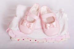 Παπούτσια λίγων ρόδινα μωρών και ενδύματα μωρών Στοκ Φωτογραφίες