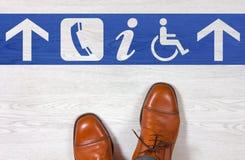 Παπούτσια ατόμων με τις κατευθύνσεις πατωμάτων Στοκ φωτογραφία με δικαίωμα ελεύθερης χρήσης