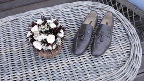 Παπούτσια ατόμων ` s του νεόνυμφου και μιας γαμήλιας ανθοδέσμης στη ημέρα γάμου πριν από τη σοβαρή τελετή απόθεμα βίντεο