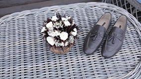 Παπούτσια ατόμων ` s του νεόνυμφου και μιας γαμήλιας ανθοδέσμης στη ημέρα γάμου πριν από τη σοβαρή τελετή φιλμ μικρού μήκους