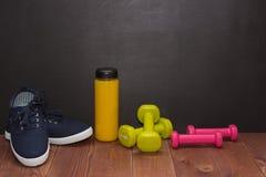 Παπούτσια, αλτήρες και μπουκάλι ικανότητας του χυμού στο ξύλινο πάτωμα Στοκ φωτογραφία με δικαίωμα ελεύθερης χρήσης
