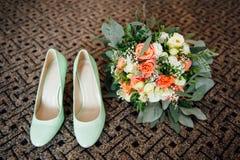 Παπούτσια γαμήλιων ανθοδεσμών και παράνυμφων στο καφετί χαλί Στοκ φωτογραφία με δικαίωμα ελεύθερης χρήσης