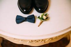 Παπούτσια δέρματος ατόμων, δεσμός τόξων και μπουτονιέρα σε ένα άσπρο επιτραπέζιο υπόβαθρο Επιχειρηματίας εξαρτημάτων ιματισμού στοκ εικόνα με δικαίωμα ελεύθερης χρήσης