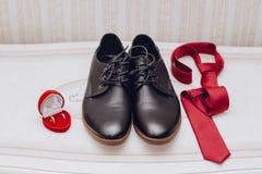 Παπούτσια, δεσμός και ένα γαμήλιο δαχτυλίδι στοκ φωτογραφία με δικαίωμα ελεύθερης χρήσης