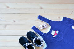 Παπούτσια και ένδυση του μωρού ή του παιδιού στην ξύλινη άποψη επιτραπέζιων κορυφών κάτω από εθνικό στοκ φωτογραφία
