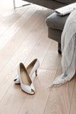 Παπούτσια και ενδύματα γυναικών που βρίσκονται μπροστά από έναν καναπέ Στοκ Φωτογραφίες
