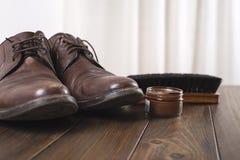 Παπούτσια και καθαρίζοντας προϊόντα στον καφετή ξύλινο πίνακα με τις κουρτίνες στο υπόβαθρο Στοκ εικόνες με δικαίωμα ελεύθερης χρήσης