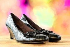 Παπούτσια μαύρων γυναικών σε ξύλινο Στοκ Εικόνες