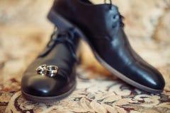 Παπούτσια μαύρων και γαμήλια δαχτυλίδια Στοκ Εικόνες