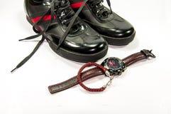 Παπούτσια μαύρων με το κόκκινα λωρίδα, το ρολόι και το βραχιόλι Στοκ Εικόνες