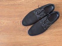 Παπούτσια μαύρων σε ένα ξύλινο πάτωμα Στοκ Εικόνες