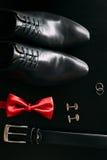 Παπούτσια μαύρων ` s, μανικετόκουμπα, γαμήλια δαχτυλίδια, μια μαύρα ζώνη και ένα α Στοκ Εικόνες