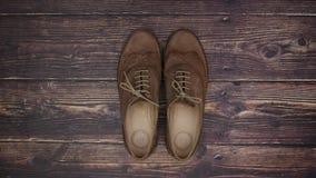 Παπούτσια με το πορτοφόλι και το τηλέφωνο στο ξύλινο υπόβαθρο - κίνηση στάσεων απόθεμα βίντεο