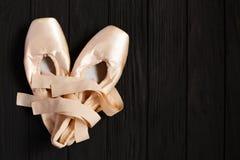 Παπούτσια μπαλέτου pointe στο μαύρο ξύλινο υπόβαθρο, ελεύθερου χώρου Στοκ Φωτογραφίες