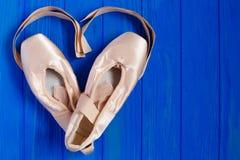 Παπούτσια μπαλέτου pointe στο φωτεινό μπλε ξύλινο υπόβαθρο με την κορδέλλα Στοκ Εικόνες