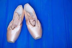 Παπούτσια μπαλέτου pointe στο φωτεινό μπλε ξύλινο υπόβαθρο Στοκ Φωτογραφία