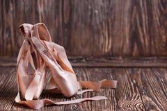 Παπούτσια μπαλέτου στο ξύλινο υπόβαθρο Στοκ Φωτογραφία