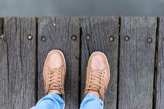Παπούτσια πάνινων παπουτσιών που περπατούν στη βρώμικη ξύλινη τοπ άποψη στοκ εικόνες
