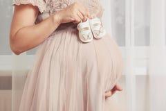 Παπούτσια παιδιών ` s εκμετάλλευσης εγκύων γυναικών Στοκ εικόνα με δικαίωμα ελεύθερης χρήσης