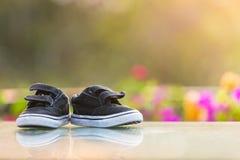 Παπούτσια παιδιών μικρών παιδιών στον πίνακα στον εγχώριο κήπο Στοκ Φωτογραφίες