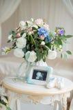 Παπούτσια παιδιών ` s και υπέρηχος του εμβρύου μωρών ` s με μια όμορφη ανθοδέσμη των λουλουδιών Στοκ εικόνες με δικαίωμα ελεύθερης χρήσης
