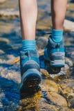 Παπούτσια πεζοπορίας - πέλμα των μποτών και των ποδιών οδοιπορίας σε ένα ρεύμα βουνών Στοκ Εικόνες