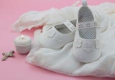 Παπούτσια, σταυρός και κερί κοριτσάκι στην άσπρη δαντέλλα με το ρόδινο backgr στοκ εικόνες