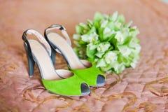 Παπούτσια της νύφης στο κρεβάτι με την πράσινη ανθοδέσμη Στοκ Φωτογραφία