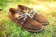 Παπούτσια των καφετιών ατόμων δέρματος, κομψά θερινά μοκασίνια στη χλόη Τα άτομα διαμορφώνουν, εξαρτήματα ατόμων και υποδήματα στοκ εικόνες