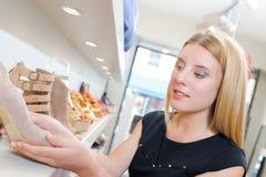 Παπούτσι γυναικείας εκμετάλλευσης στο κατάστημα στοκ εικόνες