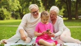 Παππούδες και γιαγιάδες και εγγονή με το smartphone απόθεμα βίντεο