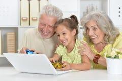Παππούδες και γιαγιάδες με τα παίζοντας παιχνίδια στον υπολογιστή εγγονών της με Στοκ Φωτογραφίες