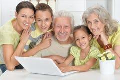 Παππούδες και γιαγιάδες με την ενήλικα κόρη και τα εγγόνια που χρησιμοποιούν το lap-top Στοκ Εικόνα