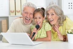 Παππούδες και γιαγιάδες με το καραόκε τραγουδιού εγγονών της με την ταμπλέτα Στοκ Φωτογραφία