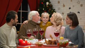 Παππούδες και γιαγιάδες που φιλούν το μικρό κορίτσι, μεγάλη οικογένεια που έχει το γεύμα Χριστουγέννων, ευτυχής χρόνος φιλμ μικρού μήκους