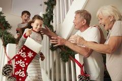 Παππούδες και γιαγιάδες που χαιρετούν τα συγκινημένα εγγόνια που φορούν τις πυτζάμες που μειώνουν τις γυναικείες κάλτσες εκμετάλλ στοκ φωτογραφίες