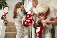 Παππούδες και γιαγιάδες που χαιρετούν τα συγκινημένα εγγόνια που φορούν τις πυτζάμες που μειώνουν τις γυναικείες κάλτσες εκμετάλλ στοκ φωτογραφία