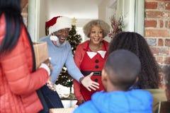 Παππούδες και γιαγιάδες που χαιρετούν τη μητέρα και τα παιδιά όπως φθάνουν για την επίσκεψη στη ημέρα των Χριστουγέννων με τα δώρ στοκ φωτογραφίες